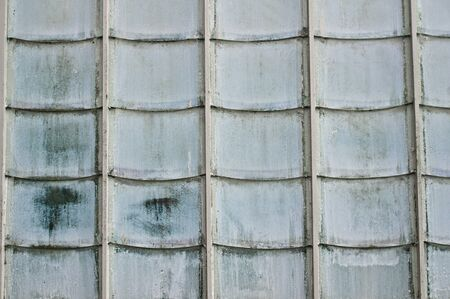 opaque: Overlapping opaque glass tiles on the exterior of a greenhouse
