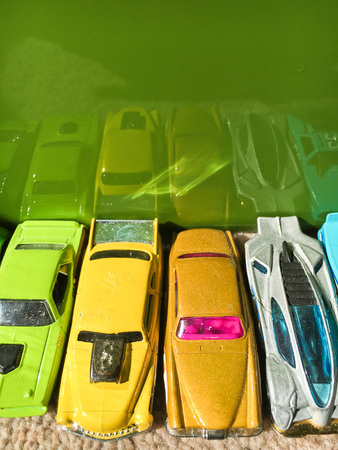 boyhood: A row of colourful toy cars reflected in a plastic surface
