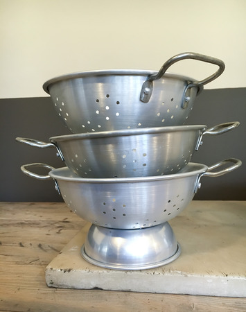 A stack of stainless steel colanders in a kitchen