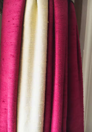burgundy colour: Pink and white curtain fabrics as a background
