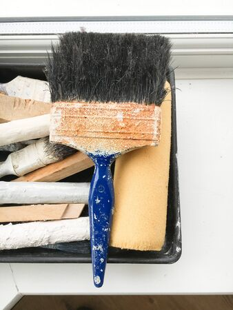 ledge: Paint brushes in a tray on a window ledge