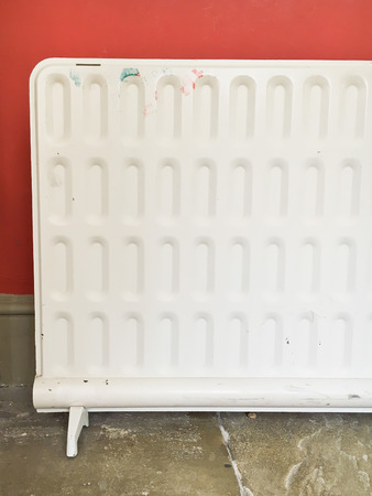 free standing: Part of a free standing electric heater against a red wall