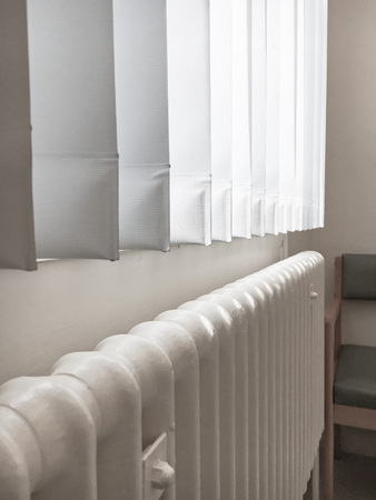 convection: Part of an old fashioned metal pipe radiator under a window with a vertical blind
