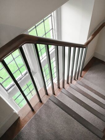 bannister: Part of an interior staircase with a wooden bannister Stock Photo