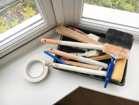 refurbishment: Paint brushes in a tray on a window ledge
