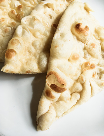naan: Slices of freshly baked naan bread on a plate