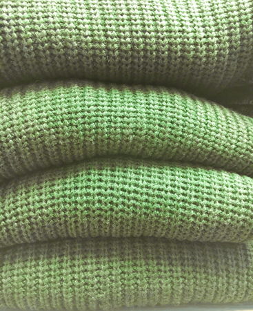 jumpers: A stack of green wool jumpers