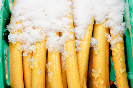 Part of a rolled up yellow hosepipe with fresh snow on it Stock Photo