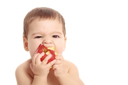 Adorable baby boy eating apple - isolated