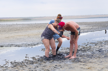 curative: Krasnodar region, Russia - 04 July, 2015: The woman rubs a hand man curative mud on the Azov Sea
