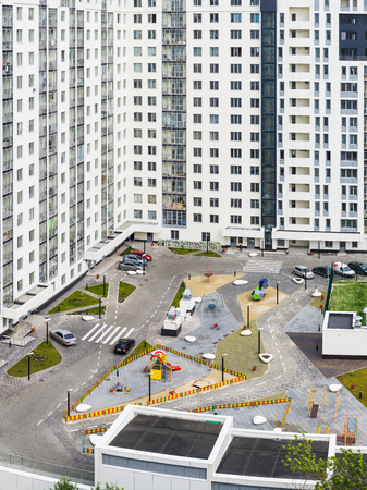 Yekaterinburg, Russia - August 01, 2017: Multistory apartment house with a modern childrens playground located in the city of Yekaterinburg in Russia