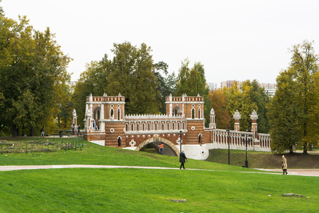 Moscow, Russia - October 09, 2017: Tourists on a walk in the Tsaritsyno Museum-Reserve near the architectural monument Figured Bridge in Moscow