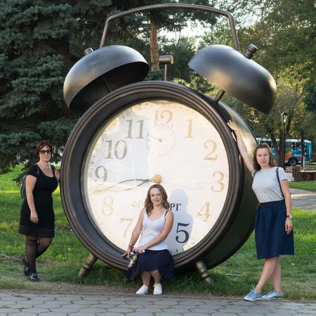 Orenburg, Russia - 26 August, 2018: People near the sculptural composition Alarm clock in Perovskiy Park in Orenburg, Russia Editorial