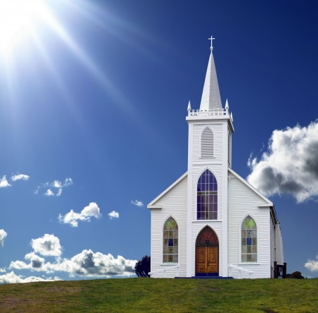 church window: Sun rays shining down on a small Christian Church on a hill.