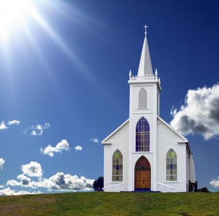 Sun rays shining nach unten auf eine kleine christliche Kirche auf einem H�gel.