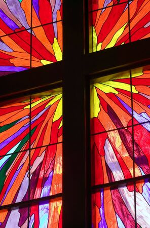 A portion of a stained glass window with wooden molding forming a Christian cross