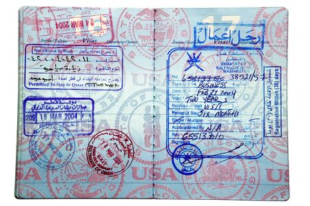 Exit and entry stamps and two Visa stamps from Oman and Qatar inside a US passport