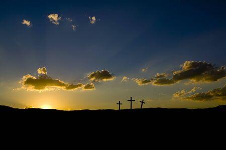 Sun rising or setting on three Christian crosses.