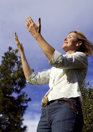thankfulness: Beautiful woman in an outdoors setting praising and worshiping Stock Photo