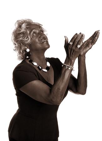 mujeres orando: Hermosa mujer afroamericana alzando sus manos en elogios.