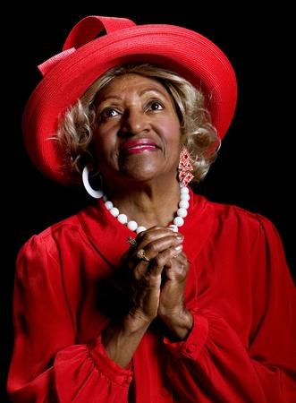 Beautiful elderly African-American woman worshiping in prayer and praise.