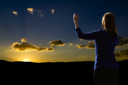 praise: Young woman with arms raised in praise worshiping at sunrise