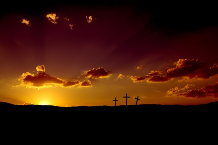 arisen: Sun rising on three Christian crosses. Stock Photo