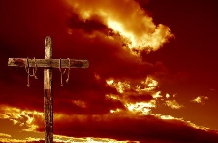 cruz de jesus: Una cruz sangrienta vacía contra un cielo nublado rojo representante de las consecuencias inmediatas de la crucifixión de Jesucristo Foto de archivo
