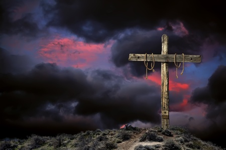 wooden cross: Bloody empty Christian cross against angry cloudy sky representing the immediate aftermath of the crucifixion of Jesus Christ. Stock Photo