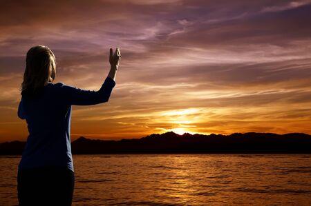 Junge Frau mit der Waffe in Lob Anbetung bei Sonnenuntergang angehoben Lizenzfreie Bilder