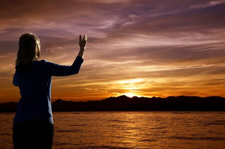 sun worship: Young woman with arms raised in praise worshiping at sunset