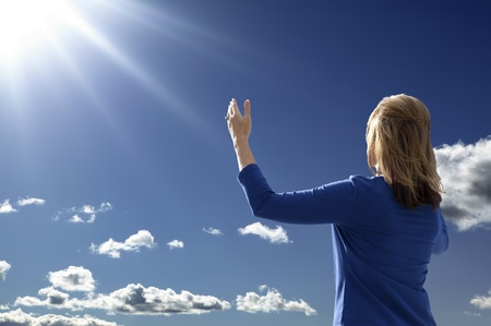 worship praise: Young lady raising her arms in worship and praise while facing the rising sun.