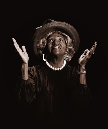 mujeres orando: Hermosa mujer afroamericana levantando sus manos en alabanza. Foto de archivo