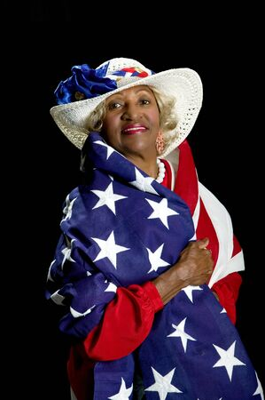 Beautiful African-American woman showing her patriotism  by being draped in an American flag. photo
