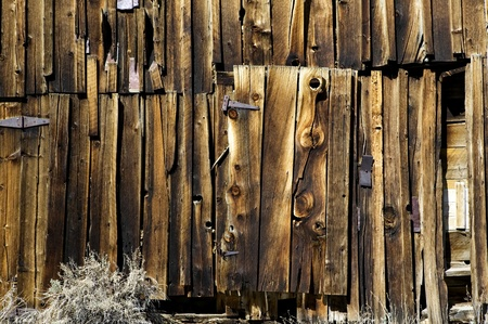 knothole: Old weathered wooden barn siding; door and door hinges