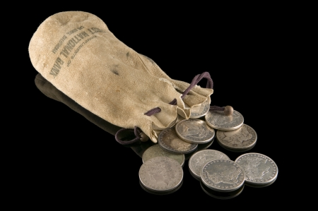 19th century: 19th Century buckskin pouch and silver dollars Stock Photo
