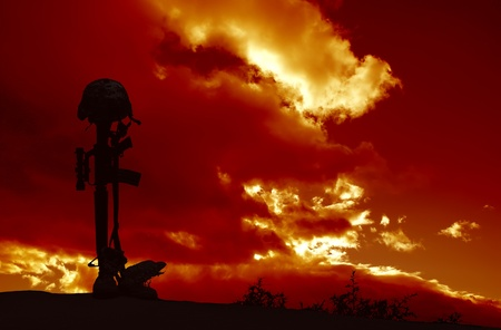 a memorial to fallen soldiers: An AR-15 rifle with combat helmet and boots silhouetted against a stormy sky as a memorial to a fallen soldier  Stock Photo