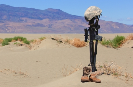a memorial to fallen soldiers: AR-15 rifle, boots and combat helmet mark the grave of a fallen soldier in a desolate land