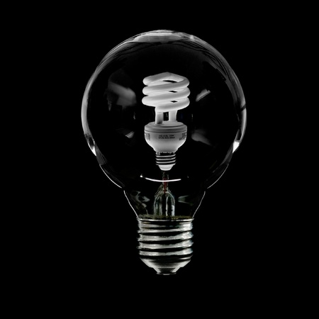 wasteful: Incandescent Light Bulb With New Compact Florescent Bulb Inside representing the transition from old wasteful incandescent to new energy saving florescent. Stock Photo