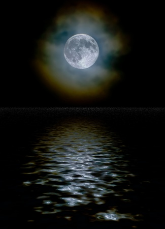 diffraction: Harvest moon as seen through a light cloud layer with ice crystal light diffraction and a water reflection Stock Photo