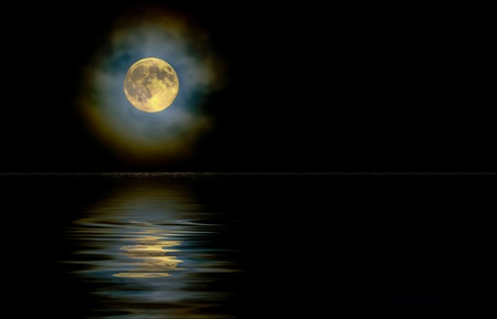 diffraction: Harvest moon as seen through a high, light cloud layer with ice crystal light diffraction reflecting on water