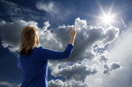 fleecy: Young woman raising her arms in worship and praise while facing the late afternoon sun. Stock Photo