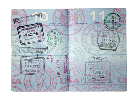 Exit and entry stamps and a Visa stamp for England and Singapore inside a U S  passport  Includes clipping path  photo