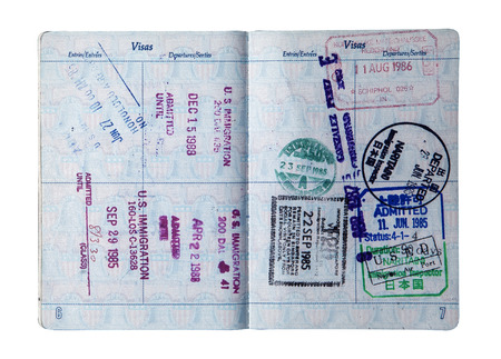 Exit and entry stamps and a Visa stamp for The Netherlands, Japan and Singapore inside a U S  passport  Includes clipping path  photo
