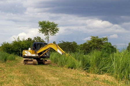 agricultural area: Yellow backhoe in the agricultural area Stock Photo