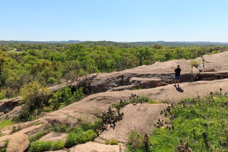 A man takes in the central Texas view from one of the hiking trails in Enchanted Rock State Park, just outside of Fredericksburg, Texas. Фото со стока - 75862341