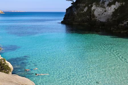 People snorkeling in turquoise paradise beach of Menorca, Baleares, Spain
