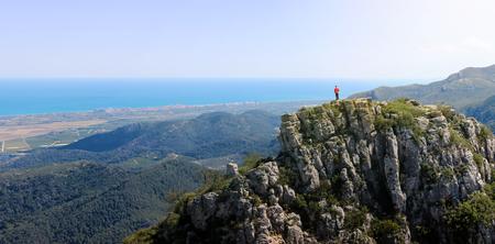 Climber on mountain overlooking the Mediterranean Sea Stock Photo