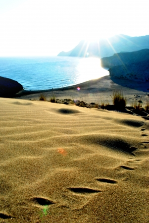 monsul: footprints in the sand with sea and mountain views