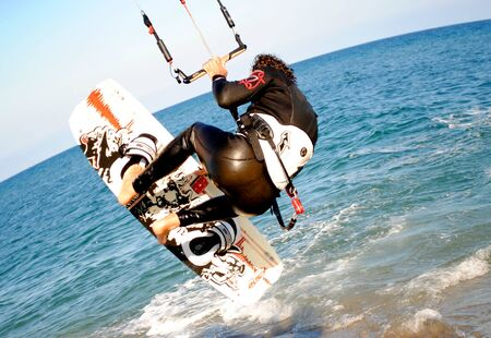 tarifa: kitesurfer landing on sunny beach Editorial